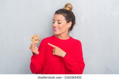Young adult woman over grey grunge wall eating chocolate chip cooky very happy pointing with hand and finger