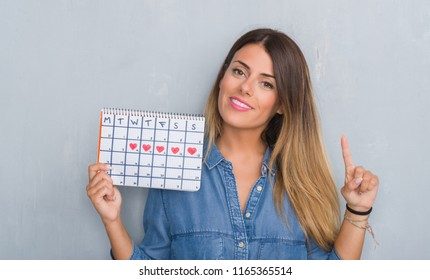 Young adult woman over grey grunge wall showing period calendar surprised with an idea or question pointing finger with happy face, number one