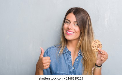 Young adult woman over grey grunge wall eating chocolate chip cooky happy with big smile doing ok sign, thumb up with fingers, excellent sign
