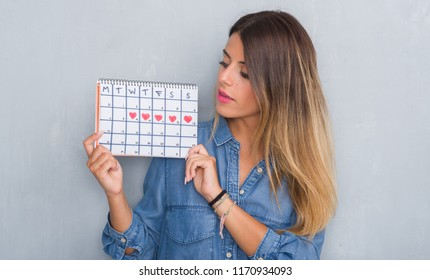 Young adult woman over grey grunge wall showing period calendar with a confident expression on smart face thinking serious