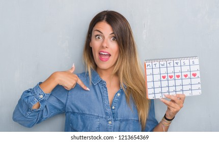 Young adult woman over grey grunge wall showing period calendar with surprise face pointing finger to himself