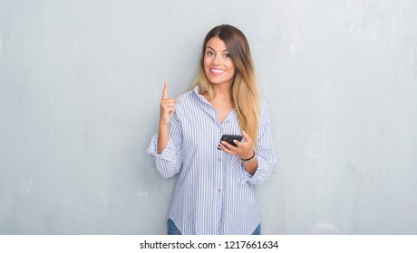 Young adult woman over grey grunge wall looking at smartphone texting a message surprised with an idea or question pointing finger with happy face, number one