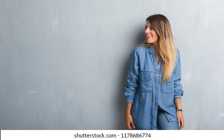 Young adult woman over grunge grey wall wearing denim outfit looking away to side with smile on face, natural expression. Laughing confident.