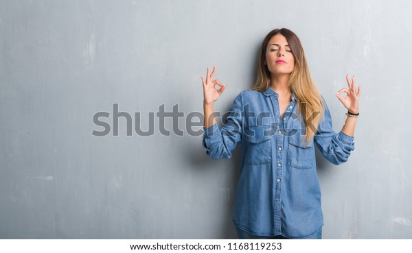 Young adult woman over grunge grey wall wearing denim outfit relax and smiling with eyes closed doing meditation gesture with fingers. Yoga concept.