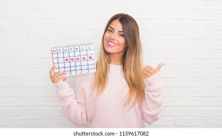 Young adult woman over white brick wall holding period calendar pointing and showing with thumb up to the side with happy face smiling