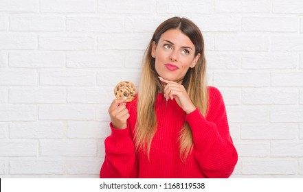 Young adult woman over white brick wall eating chocolate chip cooky serious face thinking about question, very confused idea
