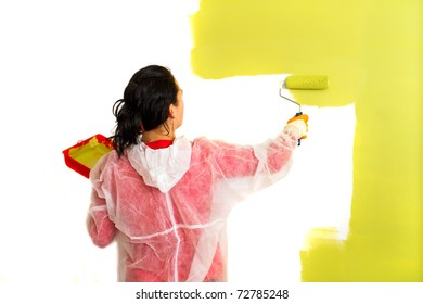 Young adult woman painting interior wall of house