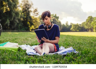 Young adult woman reading an ebook at a public park in summer