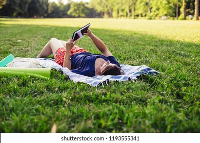 Young adult woman reading an ebook at public park