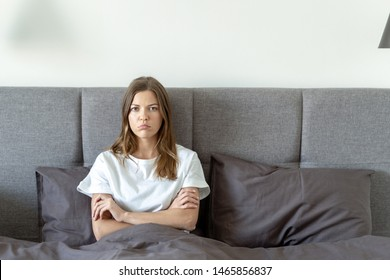 Young adult woman sitting on bed, crossed hands on chest, looking at camera offended and spending time in bedroom with copy space