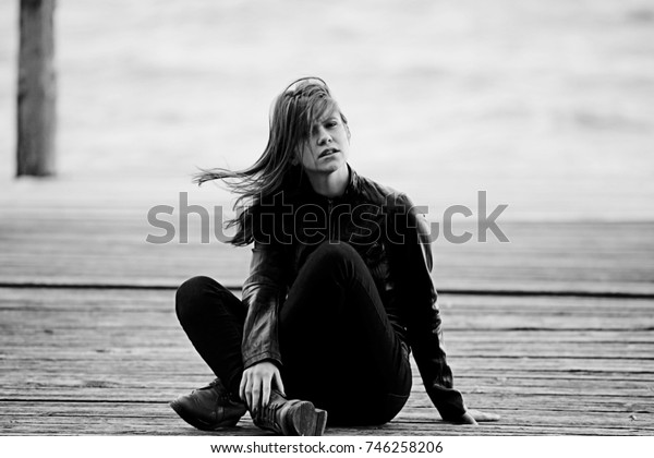 Young adult woman sitting on a wooden jetty on the river