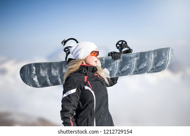 Young adult woman snowboarder holding board in hand in snow winter on the mountainside