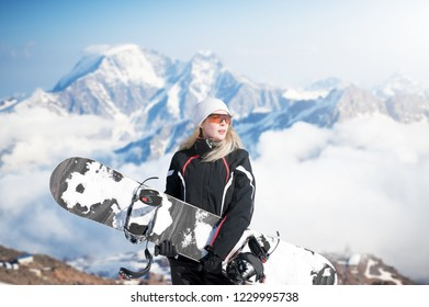 Young adult woman snowboarder holding board in hand in snow winter on the mountainside in fashion black sportswear
