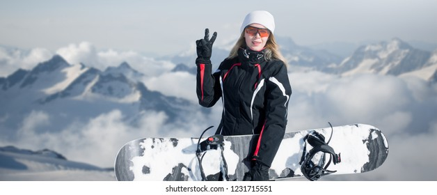 Young adult woman snowboarder holding board in hand in snow winter on the mountainside in fashion black sportswear smiles and shows two fingers