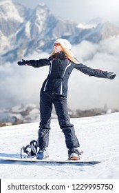 Young adult woman snowboarder standing on a snowboard one foot in the clasp of the other in the snow in winter on the mountainside. Happiness with hands to the side