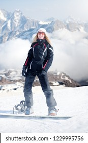 Young adult woman snowboarder standing on a snowboard one foot in the clasp of the other in the snow in winter on the mountainside