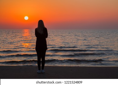 Young adult woman standing alone on sand and staring at small waves of sea and orange sunset. Girl silhouette on beach. Peaceful atmosphere in summer evening. Back view.