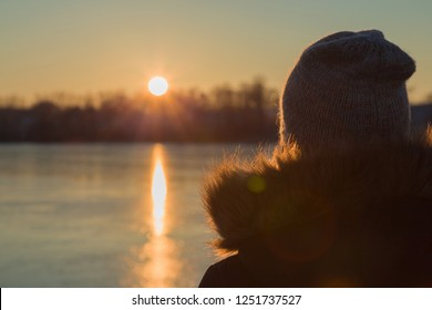 Young adult woman standing alone and staring at orange yellow sunset over frozen lake. Girl's silhouette closeup. Peaceful atmosphere in winter evening. Back view.