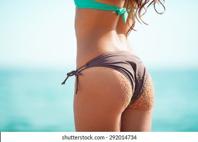 Young adult woman standing on shore dressed in a bikini. Photography shows her back and her buttocks on which are the grains of sand.