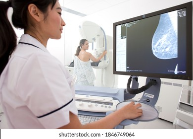 A young adult woman taking the mammogram test on a machine in a clinic while being examined by a professional radiologist in a lab coat through a high definition x-ray monitor