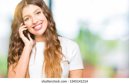 Young adult woman taking on the phone with a happy face standing and smiling with a confident smile showing teeth