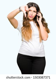 Young adult woman taking on the phone with angry face, negative sign showing dislike with thumbs down, rejection concept
