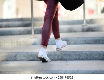 Young adult woman walking up the stairs