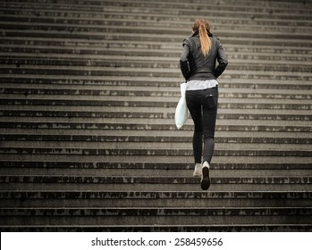 Young adult woman walks up the stairs (in the rain)