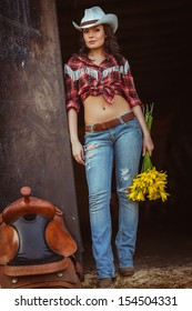 young adult woman wearing country style wear posing near door with flowers and saddle