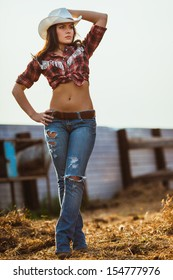 young adult woman wearing country style posing on farmland