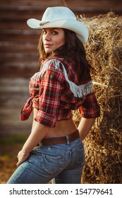 young adult woman wearing country style posing on farmland, closeup portrait