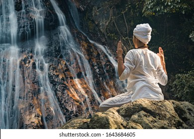 Young adult woman in white clothes sits on a rock against the background of a waterfall and practices yoga