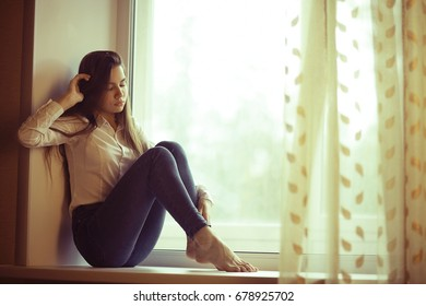 young adult woman at the window