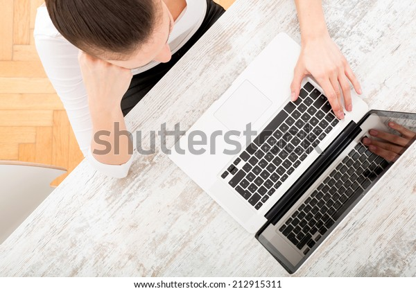A young adult woman working on a laptop.