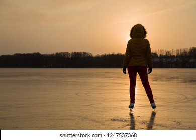 Young adult woman's silhouette on skates standing on lake ice  and looking at light orange yellow sunset of winter evening. Enjoying sport in cold weather. Outdoor activities on weekends. Back view.
