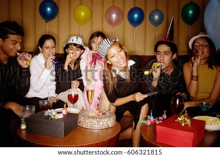 Young Adults Celebrating Birthday Wearing Party Hats