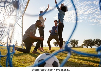 Young adults cheering a scored goal at football game