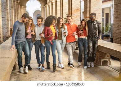 young adults converse and joke together using their smartphones walking under the arcades of a European city. Social media concept.