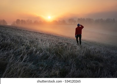 Young adventurer man standing in nature and looking to the beautiful landscape and morning scenery - sunrise over forest and misty meadow covered by frozen winter grass. Few days before christmas.