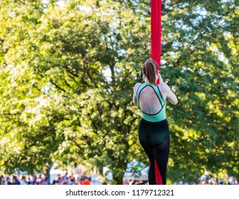 Young Aerial acrobatic dancer is climbing a red silk ribbon