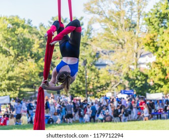 A young aerial acrobatic dancer is hanging upside down on her legs