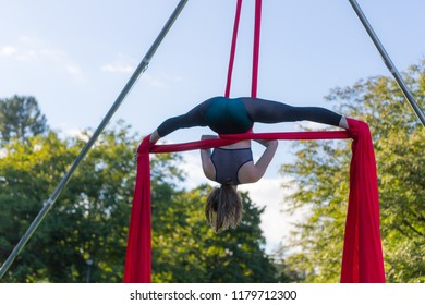 Young Aerial acrobatic dancer viewed against the blue sky is doing a split