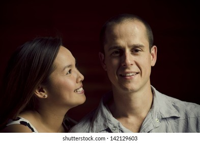 Young affectionate couple with attractive woman looking at her partner. Male is caucasian, female is asian.