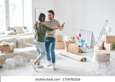 Young affectionate couple in casualwear dancing in living-room after removing to new flat or house with packed stuff on background