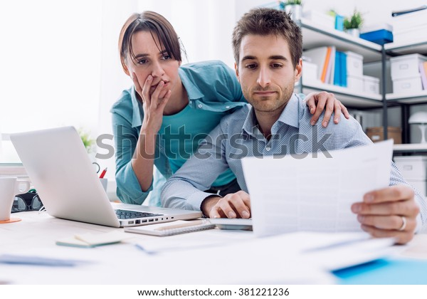 Young affectionate couple at home checking expensive bills, they are calculating balance and costs