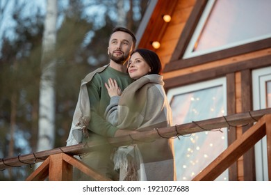 Young affectionate couple wrapped in plaid standing against country house on background of trees in the forest and looking at sunrise