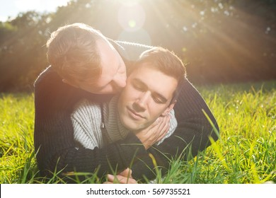Young affectionate gay couple lying on green grass
