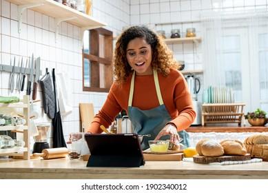Junge affikanische Amerikanerin lernt online Kochkurs über Tablet-Computer in der Küche zu Hause