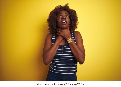 Young african afro woman wearing striped t-shirt over isolated yellow background shouting and suffocate because painful strangle. Health problem. Asphyxiate and suicide concept.