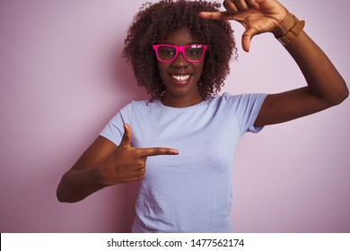 Young african afro woman wearing t-shirt glasses over isolated pink background smiling making frame with hands and fingers with happy face. Creativity and photography concept.